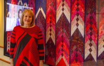 Lois DeGiulio standing in front of her homemade quilt